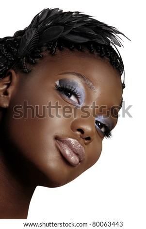 beautiful young African woman portrait wearing feather headband and dark smoky eyeshadow over white background - stock photo