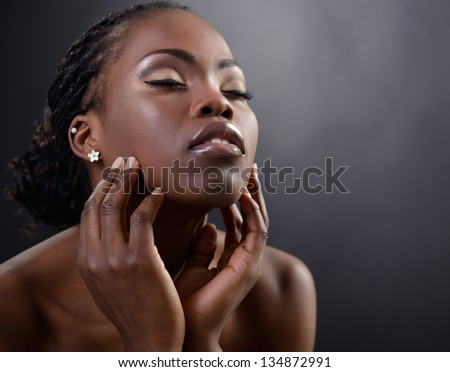 Beautiful young african woman posing at studio, face with hand portrait over dark background - stock photo