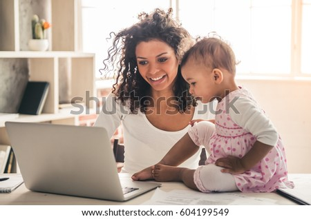 Beautiful young Afro American woman and her cute baby are using a laptop and smiling while spending time together at home