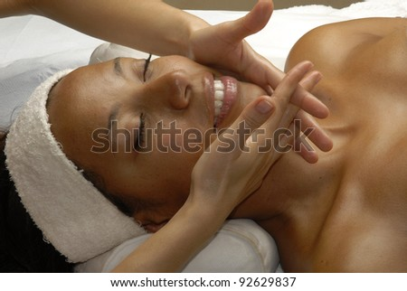 Beautiful young Afro american woman getting a face treatment at beauty salon. Beautiful young black woman getting a face treatment at beauty salon. - stock photo