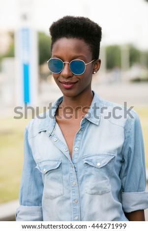 beautiful young and cool black lady walking on the street, in jeans shirt and nice haircut - stock photo