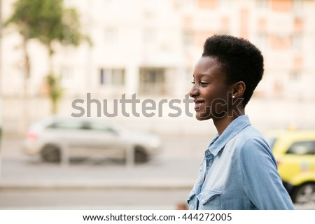 beautiful young and cool black lady walking on the street, in jeans shirt and nice haircut