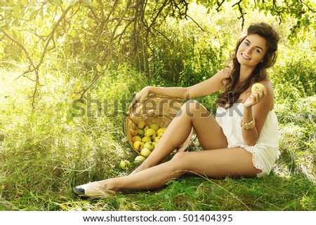 Beautiful, young and happy woman in garden during a picking apples