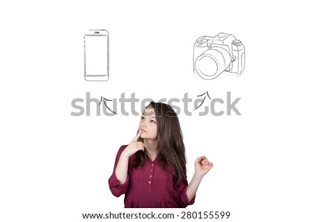 Beautiful young and pretty woman taking a decision (choose) between smartphone and camera - isolated on white background - stock photo