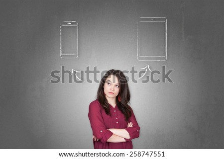 Beautiful young and pretty woman taking a decision (choose) between tablet and smartphone - stock photo