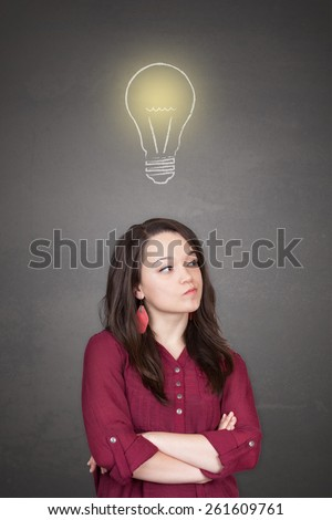 Beautiful young and pretty woman thinking (have no idea) in front of light idea bulb concept - stock photo