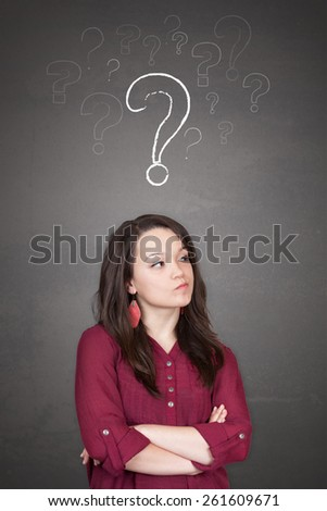 Beautiful young and pretty woman thinking (have no idea) in front of question marks concept - stock photo