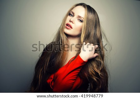 Beautiful young and sexy caucasian woman model with deep blue eyes and sensitive lips posing at studio in the light flashes. Great long natural hair. - stock photo