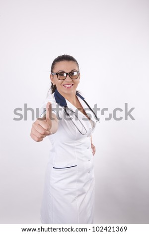 Beautiful young and sexy female doctor pointing thumb up.