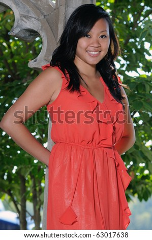 Beautiful young Asian American woman in orange dress standing in castle like courtyard