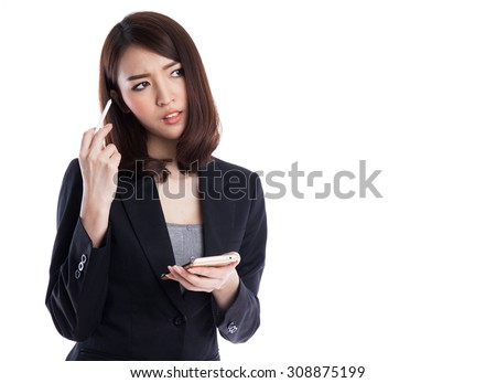 Beautiful young asian business woman typing and thinking with stylus on device or smartphone, looking to copy space, isolated on white background - stock photo