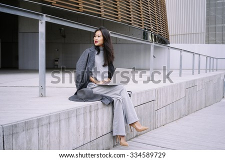 Beautiful young Asian business woman working next to the business center during lunch break - stock photo
