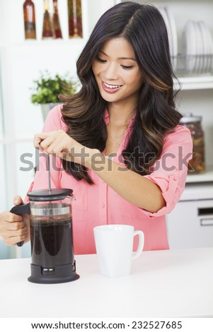 Beautiful young Asian Chinese woman or girl at home in her kitchen smiling and making a cup or mug of coffee with a french press or cafetiere - stock photo