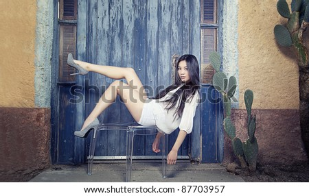 Beautiful young Asian fashion model posing on chair - stock photo