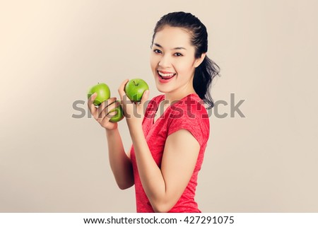 Beautiful young Asian fitness woman happy smile hold green apple. Healthy lifestyle. - stock photo