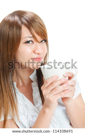 Beautiful young Asian girl holding a cup of tea/coffee over white background - stock photo