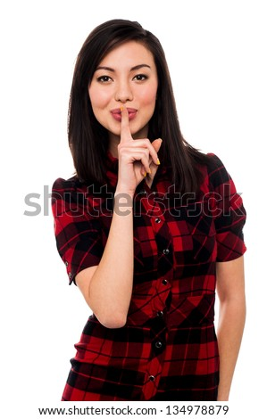 Beautiful young asian girl with finger on her lips gesturing shh. - stock photo