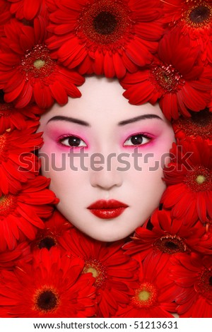Beautiful young asian girl with stylish make-up and red flowers around face - stock photo