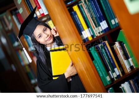 Beautiful young asian graduate holding book - stock photo