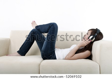 beautiful young asian listening to music on a sofa - stock photo
