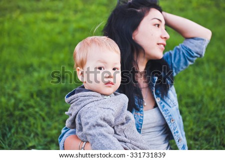 Beautiful young asian mom with freckles and son relaxing outdoors. Mother brunette with dark hair and son is blond. Serious boy looking at camera. Unusual appearance, diversity and heredity concept  - stock photo
