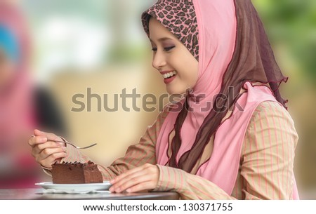 Beautiful young Asian Muslim woman smiles while eating cake