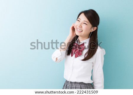 Beautiful young asian school girl listening music - stock photo