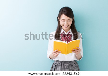 Beautiful young asian school girl who reads a book