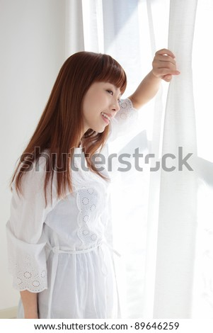 Beautiful young Asian woman by the window