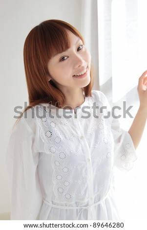 Beautiful young Asian woman by the window - stock photo