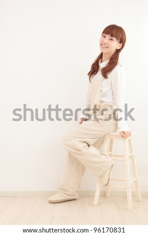 Beautiful young Asian woman dressed in overalls sit in a bright room. - stock photo