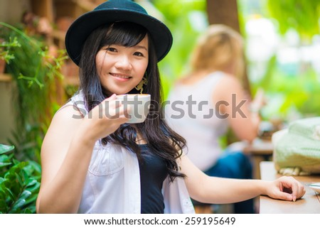 Beautiful young asian woman drinking coffee smiling in cafe.