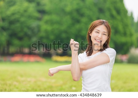 Beautiful young asian woman exercising in the park - stock photo