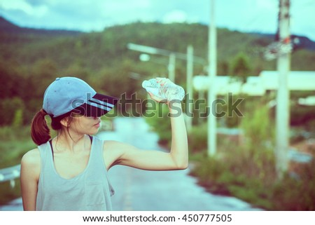 Beautiful young asian woman exercising in the park, Holding water bottle in hand.Relaxing on the road. - stock photo