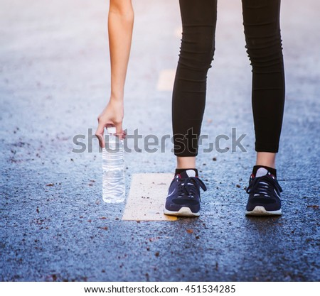 Beautiful young asian woman exercising in the park, Holding water bottle in hand.Relaxing on the road