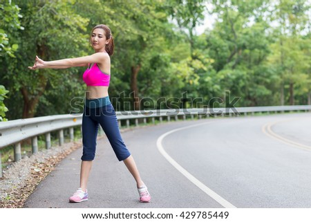 Beautiful young asian woman exercising on the road.