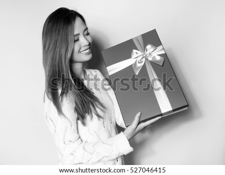 beautiful young asian woman holding present