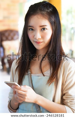 beautiful young asian woman holding smart phone - stock photo