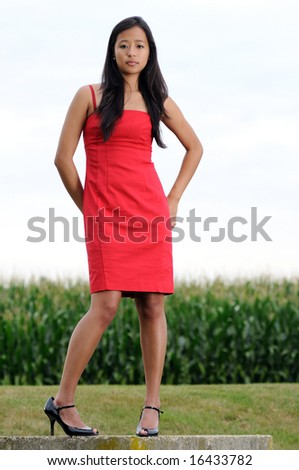 Beautiful young Asian woman in red dress in front of corn field - stock photo