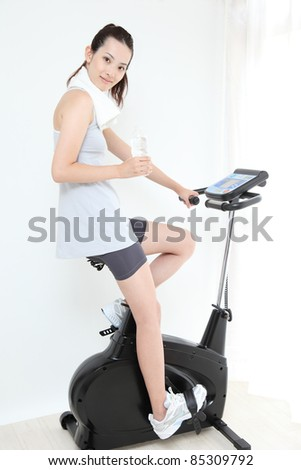 Beautiful young Asian woman Indoor bicycle cycling - stock photo