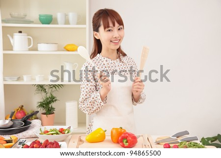 Beautiful young Asian woman is being prepared to make a salad in the kitchen. - stock photo
