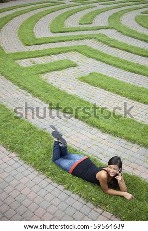 Beautiful young Asian woman lies down on the grass of a park labyrinth while enjoying a conversation on her cellphone. Vertical shot. - stock photo