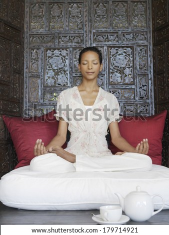 Beautiful young Asian woman meditating sitting in the lotus position in front of an ornate wooden screen with her eyes closed, a tranquil serene expression and a lovely peaceful smile - stock photo