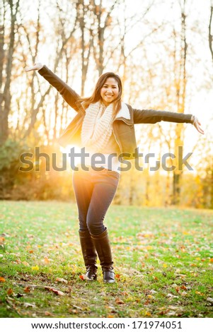 Beautiful young Asian woman outdoors in the fall with arms outstretched happy and carefree - stock photo