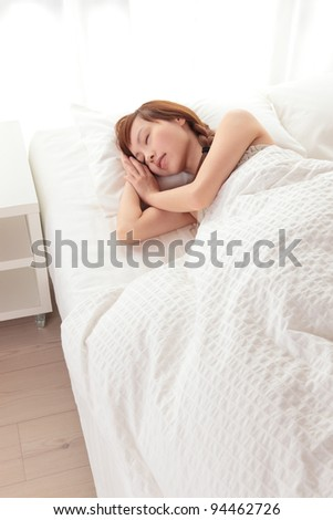 Beautiful young Asian woman sleeping on the bed - stock photo