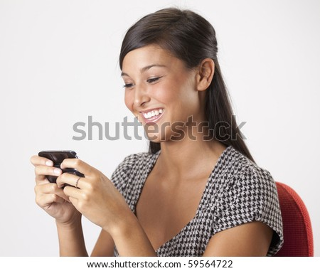 Beautiful young Asian woman smiles while writing a text message on her mobile phone. Horizontal shot. - stock photo
