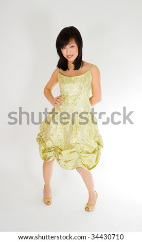 Beautiful young asian woman standing in gold dress and smiling - stock photo
