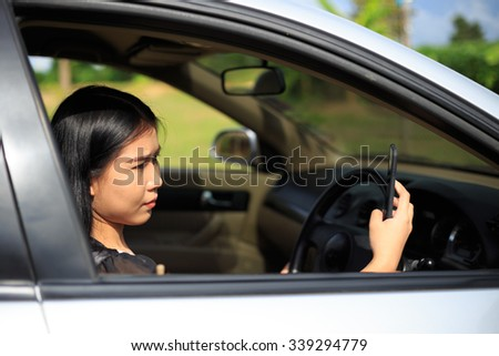 Beautiful young asian woman using map in mobile application in a car - stock photo
