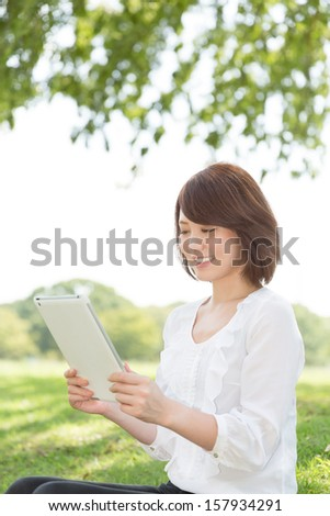 Beautiful young asian woman using tablet computer