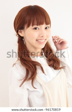 Beautiful young Asian woman wearing an apron - stock photo